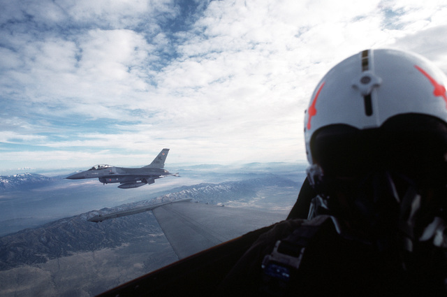 An air-to-air left side view of an F-16 Falcon aircraft assigned to the 388th Tactical Fighter Wing as seen from the cockpit of another F-16 during a mission out of Hill Air Force Base