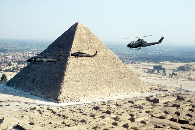 AN air-to-air left side view of two UH-60 BlackHawk and one AH-1G Cobra (rear) helicopters in front of a pyramid during exercise Bright Star '82