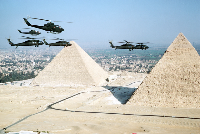 AN air-to-air right side view of UH-60 BlackHawk and AH-1G Cobra helicopters in front of the pyramids during exercise Bright Star '82