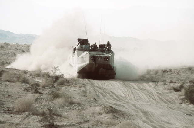An AMTRAC (LVTP-7) moves pretty fast down a rusty road. The Marines in the LVTP-7 have just received orders from the command post and are responding. This is part of Operation CAX 1-2-82, held at the Marine Corps Air-to-Ground Combat Center
