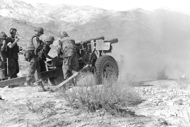An artillery gun team from Btry. C, 5th Bn., 10th Marines, fires their 105mm howitzer during Operation CAX-1-2-82