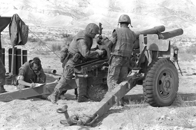 An artillery gun team from Btry. C, 5th Bn., 10th Marines, prepares to fire their 105mm howitzer during Operation CAX-1-2-82
