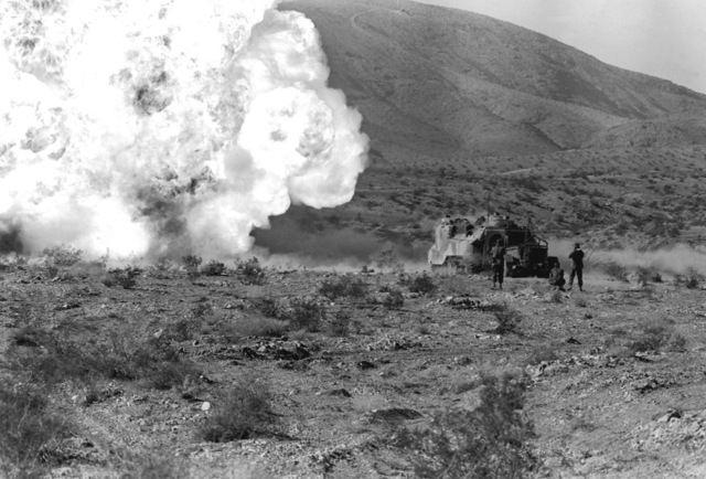 An explosion is set off in front of an LVTP-7 tracked landing vehicle during Operation CAX-1-2-82. The three Marines standing behind the LVTP-7 protect ears from the noise