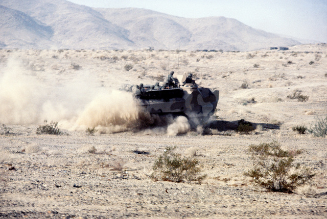 An LVTP-7 tracked landing vehicle loaded with troops speeds across the desert during Operation CAX 1-2-82 at the Marine Corps Air-to-Ground Combat Center