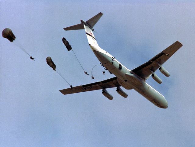 Bottom view of a C-141 Starlifter aircraft dropping personnel during exercise Bright Star '82