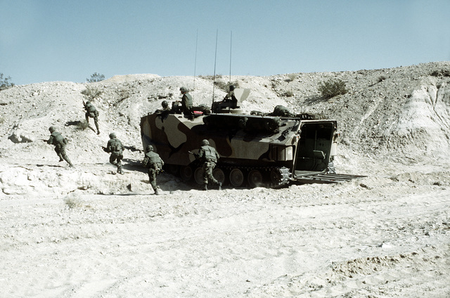 Combat-ready Marines from Co. A, 1ST Bn., 8th Marines, 2nd Marine Div., disembark an LVTP-7 tracked landing vehicle to assault an enemy bunker on the beach. The Marines are participating in Operation CAX 1-2-82 at the Marine Corps Air-to-Ground Combat Center
