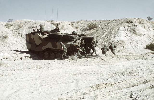 Combat-ready Marines from Co. A, 1ST Bn., 8th Marines, disembark an LVTP-7 tracked landing vehicle as they prepare to assault a hill during Operation CAX 1-2-82 at the Marine Corps Air-to-Ground Combat Center