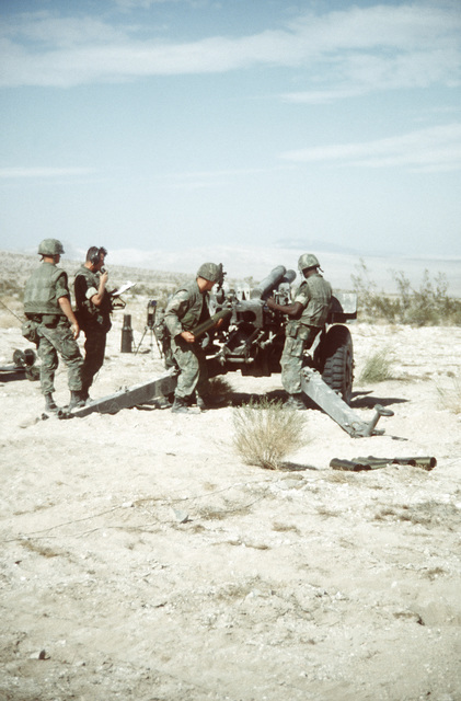 Combat-ready Marines in this 105mm howitzer section load the gun during a live fire mission. The Marines are participating in Operation CAX 1-2-82 at the Marine Corps Air-to-Ground Combat Center