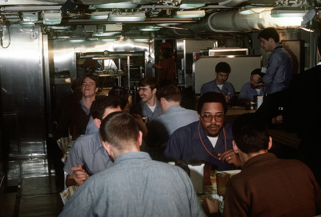 Crewmen eat in the crew mess during precommissioning duty aboard the nuclear-powered fleet ballistic missile submarine OHIO (SSBN-726). The OHIO was built by General Dynamics Corp