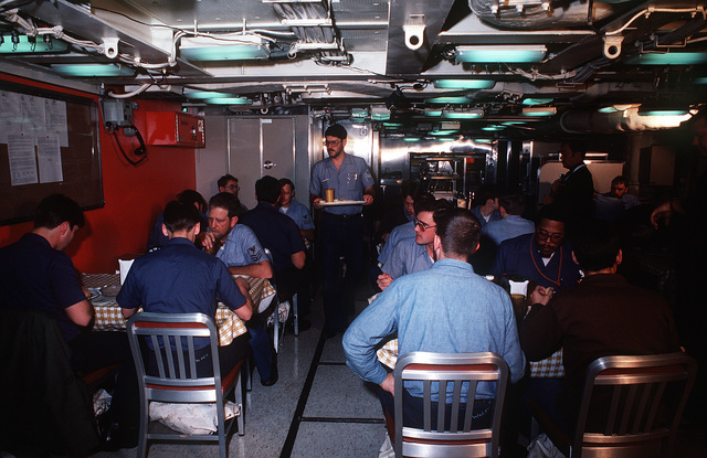 Crewmen eat in the crew's mess during precommissioning duty aboard the nuclear-powered ballistic missile submarine OHIO (SSBN-726). The submarine was built by General Dynamics Corp