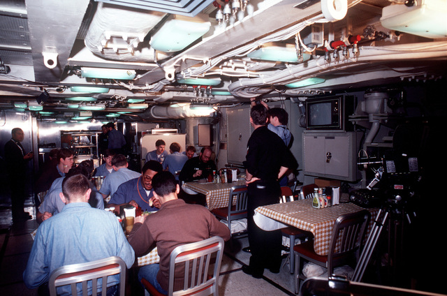 Crewmen eat in the dining hall during precommissioning duty aboard the nuclear-powered ballistic missile submarine OHIO (SSBN-726). The submarine was built by General Dynamics Corp