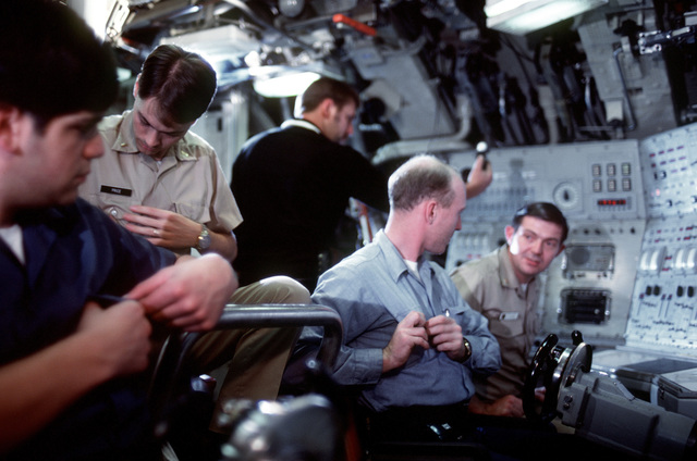 Crewmen in the control room prepare for a simulated diving operation during precommissioning activities aboard the nuclear-powered ballistic missile submarine OHIO (SSBN-726). The submarine was built by General Dynamics Corp
