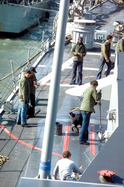 Crewmen paint the deck of a U.S. Navy ship