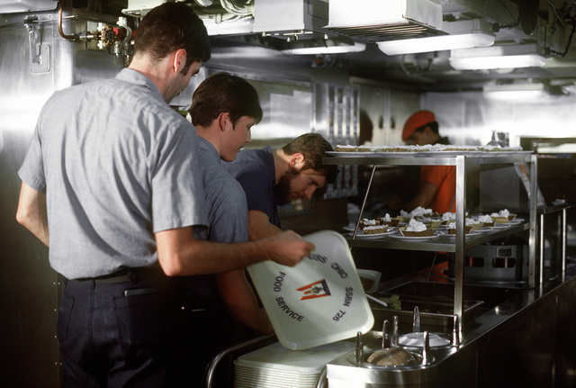 Crewmen stand in line to get a meal in the crew mess aboard the nuclear-powered fleet ballistic missile submarine OHIO (SSBN-726). The crewmen are assigned to precommissioning duty aboard the submarine built by General Dynamics Corp