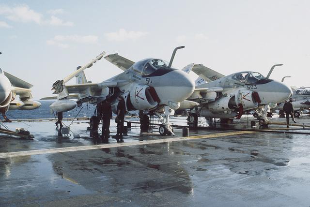 Crewmen wash A-6E Intruder aircraft on the flight deck of the aircraft carrier USS MIDWAY (CV 41)