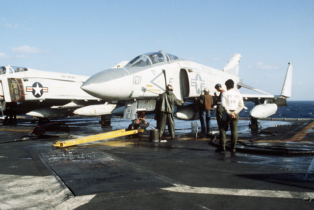 Crewmen wash a Fighter Squadron 161 F-4S Phantom II aircraft aboard the aircraft carrier USS MIDWAY (CV 41)