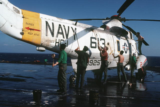 Crewmen wash an SH-3H Sea King helicopter from Helicopter Combat Support Squadron 1 on the flight deck of the aircraft carrier USS MIDWAY (CV 41)