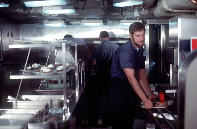 Crewmen with lunch trays in the dining hall during precommissioning duty aboard the nuclear-powered ballistic missile submarine OHIO (SSBN-726). The submarine was built by General Dynamics Corp