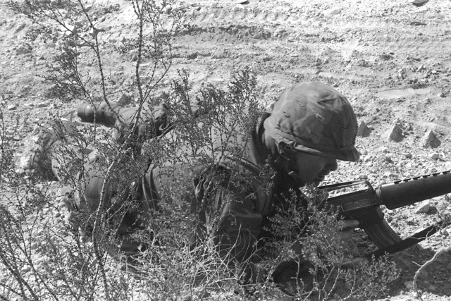 During Operation CAX-1-2-82, CPL Smith of Co. A, 1ST Bn., 8th Marines, moves into position to assault the objective