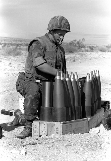 During Operation CAX-1-2-82, LCPL Jones of Hotel Company, 1ST Battalion, 10th Marines, prepares the rounds (ammunition) for his 105mm howitzer team