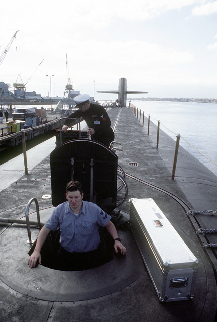 Electronics Technician 2nd Class (Submarines) (ET2) (SS) M. Pittinger, in the hatchway, and a Navy Industrial Relations Activity (NIRA) crewmen load equipment aboard the nuclear-powered ballistic missile submarine OHIO (SSBN-726) during precommissioning preparations. The submarine was built by General Dynamics Corp
