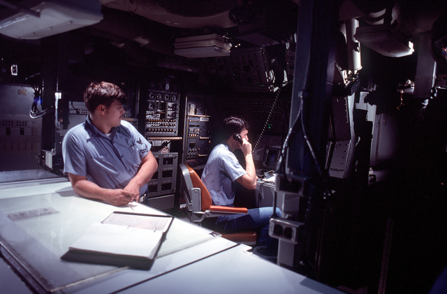 Electronics Technicians 2nd Class (Submarines) (ET2) (SS) Steven W. Lockhart Jr., using the telephone, and James R. Fackler man their stations during a precommissioning exercise aboard the nuclear-powered ballistic missile submarine OHIO (SSBN-726). The submarine was built by General Dynamics Corp