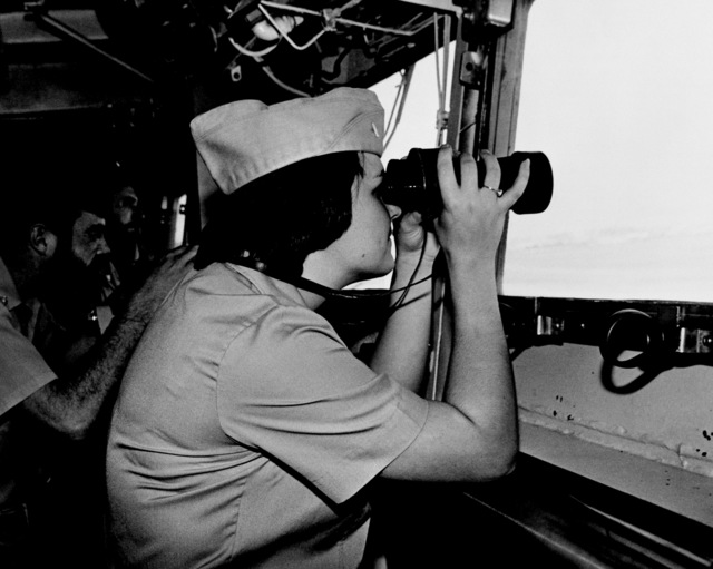 ENSIGN Roberta McIntyre, the first female to qualify as a surface weapons officer, scans the horizon from the bridge of the submarine tender USS DIXON (AS 37) where she serves as electrical officer
