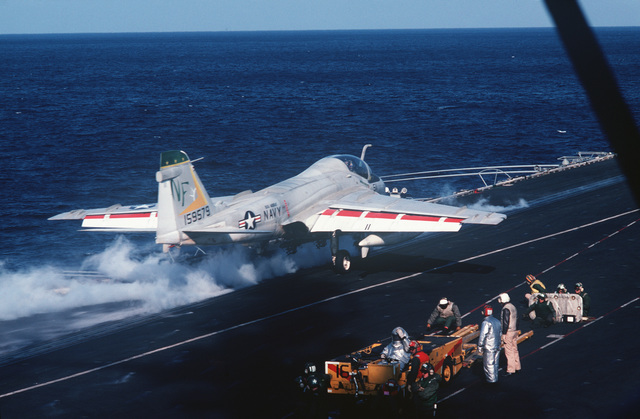 Fire fighters stand by in a crash vehicle as an A-6E Intruder aircraft is catapulted from the flight deck of the aircraft carrier USS MIDWAY (CV 41)