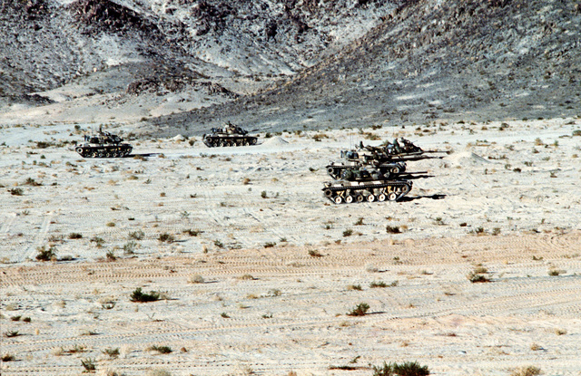 Five M60A1 tanks move into position for an assault on a bunker during Operation CAX 1-2/82 at the Marine Corps Air-to-Ground Combat Center