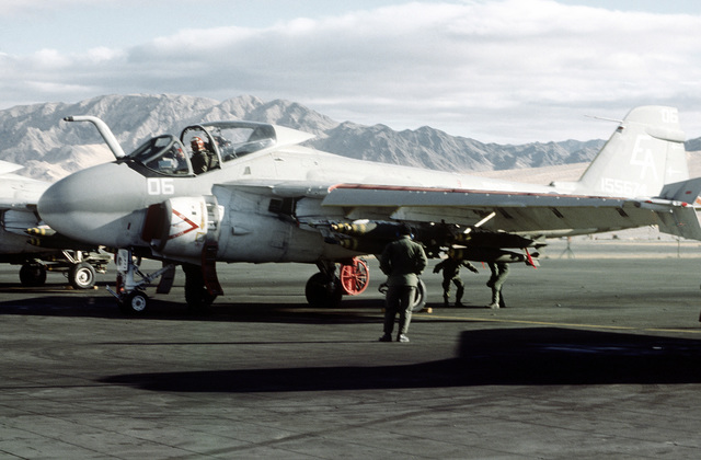 Flight line crew members prepare a bomb-loaded A-6E Intruder aircraft for a mission during Operation CAX 1-2-82, held at the Marine Corps Air-to-Ground Combat Center