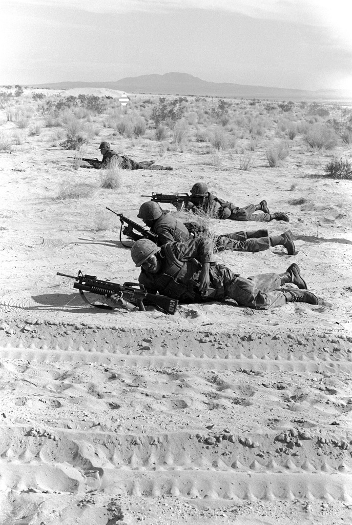 Four combat ready Marines assault their objective by using live fire from their M-16A1 rifles and M-203 40mm grenade launchers mounted on their rifles. The Marines are a part of Kilo Company, 3rd Battalion, 2nd Marines and are participating in Operation CAX-1-2-82