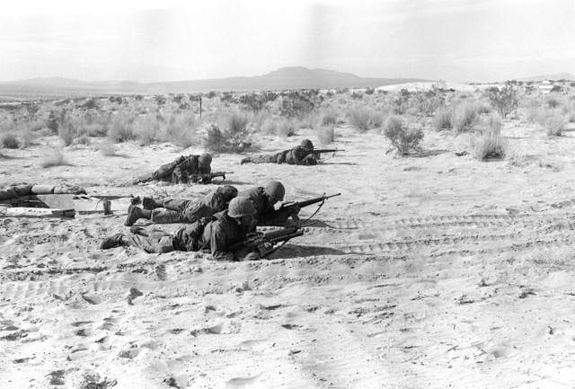 Four combat ready Marines from Weapons Company, 1ST Battalion, 8th Marines, are in the prone position with their M-16A1 rifles and an M-203 40mm grenade launcher attacked to the first rifle. The Marines are assaulting their objective during Operation CAX-1-2-82