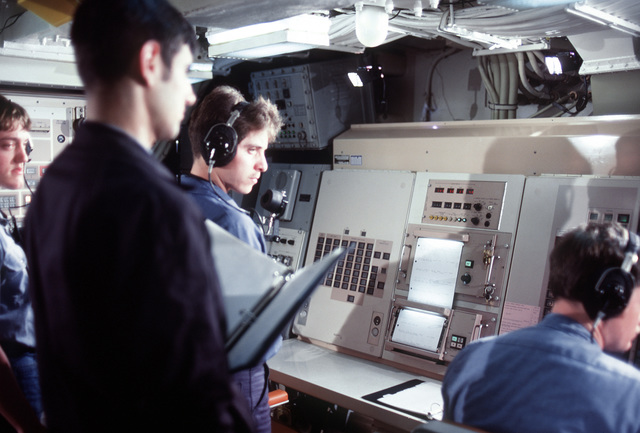 Four crew members participate in a simulated missile firing in the control room during precommissioning activities aboard the nuclear-powered ballistic missile submarine OHIO (SSBN-726). The participants are, from left, MT2 (SS) G. Lindquist, FTB2 (SS) Brian Douglass, FTB3 (SS) Brian King and FTB1 (SS) David Starnes