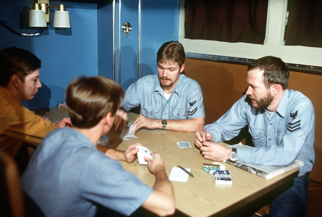 Four crewmen play cards game in the crew lounge aboard the nuclear-powered fleet ballistic missile submarine OHIO (SSBN-726). The crewmen are assigned to precommissioning duty aboard the submarine built by General Dynamics Corp