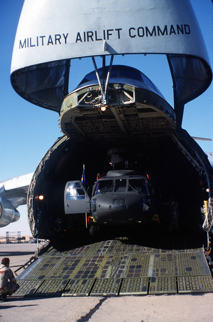 Front view of a CH-3 Jolly Green Giant helicopter being unloaded from a C-5 Galaxy aircraft during exercise Bright Star '82