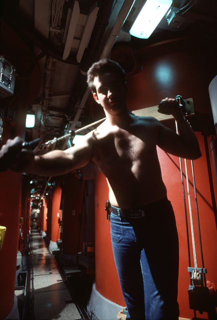 Interior Communications Electrician 1ST Class (Submarines) (ICI) (SS) D. M. Geske uses exercise equipment while he is assigned to precommissioning duty aboard the nuclear-powered ballistic missile submarine OHIO (SSBN-726). The ship was built by General Dynamics Corp