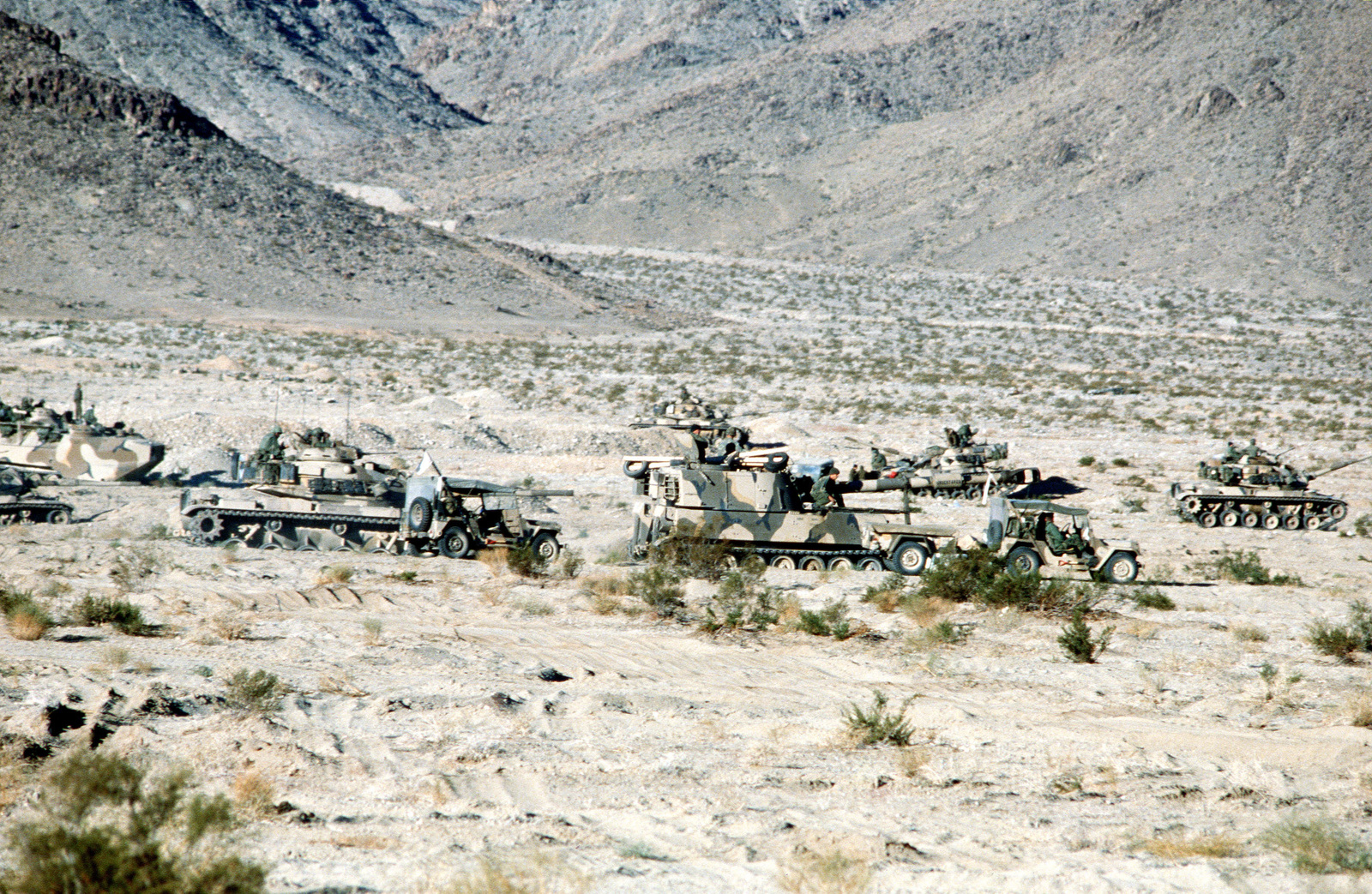 Many pieces of Marine Corps equipment such as M60A1 tanks, LVTC7 track landing vehicles, M109 155 mm self-propelled howitzers and M151 jeeps, are staged here during a commander's briefing. The equipment is being used in Operation CAX 1-2-82 at the Marine Corps Air-to-Ground Combat Center