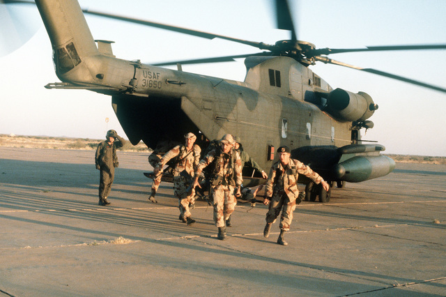 Military personnel unload supplies from a CH-53 helicopter during exercise Bright Star '82