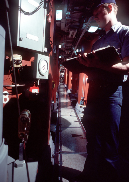 Missile Technician SEAMAN (MTSN) M. A. Frazer checks a gauge in the lower ballistic missile compartment of the nuclear-powered ballistic missile submarine OHIO (SSBN-726) during precommissioning preparations. The submarine was built by General Dynamics Corp