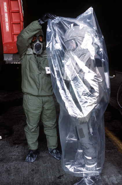 MSGT John D. Wogoman helps pilot MAJ Willie Register put on his protective plastic body bag after his mission aboard an F-4 Phantom II aircraft. Wogoman and Register are both wearing chemical warfare gear for training