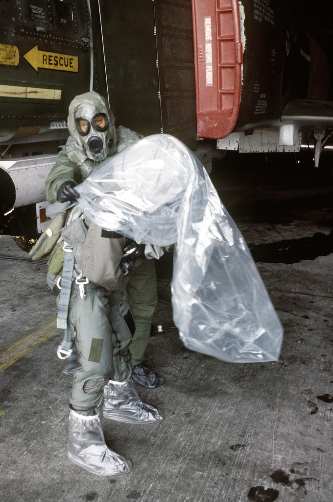 MSGT John D. Wogoman helps pilot MAJ Willie Register take off his protective body bag prior to his mission aboard an F-4 Phantom II aircraft. Wogoman and Register are both wearing chemical warfare gear for training