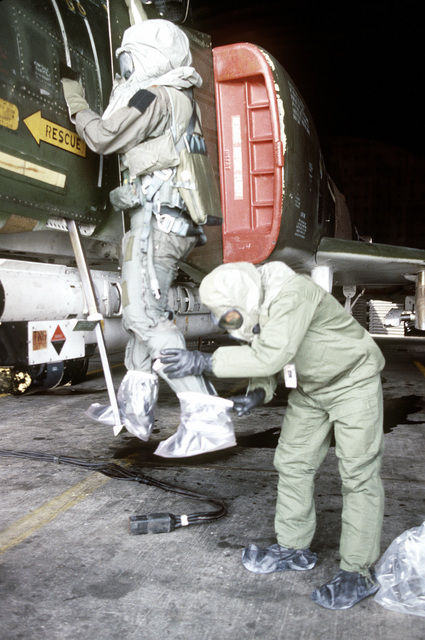 MSGT John D. Wogoman puts protective plastic boot covers on pilot MAJ Willie Register after his mission aboard an F-4 Phantom II aircraft. Wogoman and Register are both wearing chemical warfare gear for training