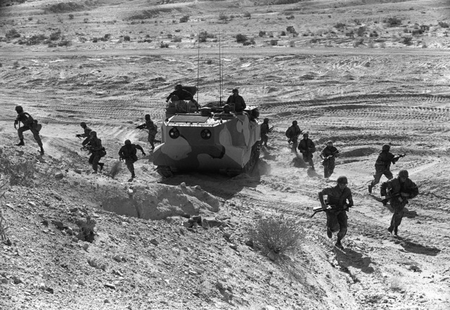 Part of 3rd Plt., Co. A, 1ST Bn., 8th Marines, debark an LVTP-7 tracked landing vehicle and prepare to assault their objective. The Marines are participating in Operation CAX-1-2-82