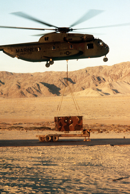Pilots from Marine Medium Helicopter Squadron 161 (HMM-161) use a CH-53 Sea Stallion helicopter to airlift a communications trailer to a command post. The Marines are participating in Operation CAX 1-2-82 at the Marine Corps Air-to-Ground Combat Center