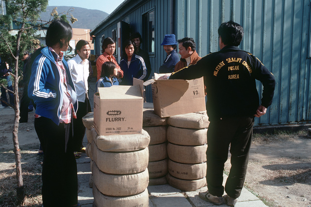 Residents of a Vietnamese refugee camp examine supplies provided to them from the aircraft carrier USS MIDWAY (CV 41)