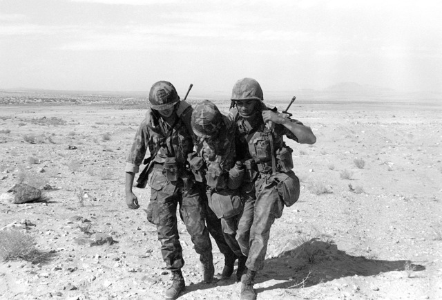 SGT Smith and CPL Davis assist a third Marine from Alpha Company, 1ST Battalion, 8th Marines, by using the two-man carry. This is part of their training in first-aid during Operation CAX-1-2-82