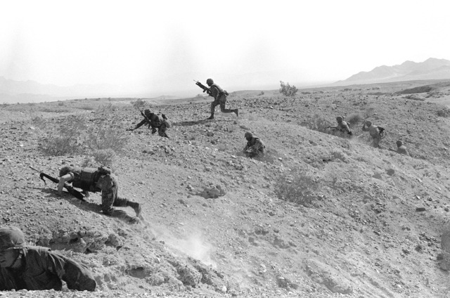 Some members of Co. L, 3rd Bn., 2nd Marines, move out and over a hill during Operation CAX-1-2-82