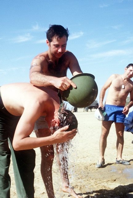 SSGT Steve Seldin, 438th Field Maintenance Squadron, helps 2nd LT. Steve Burgess, Headquarters, Military Airlift Command, wash his hair in a helmet during exercise Bright Star '82