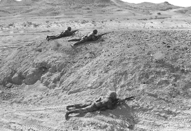 Three combat ready Marines from Co. K, 3rd Bn., 2nd Marines, are in the prone position with their M-16A1 rifles. They are awaiting word to move forward and assault their objective during Operation CAX-1-2-82
