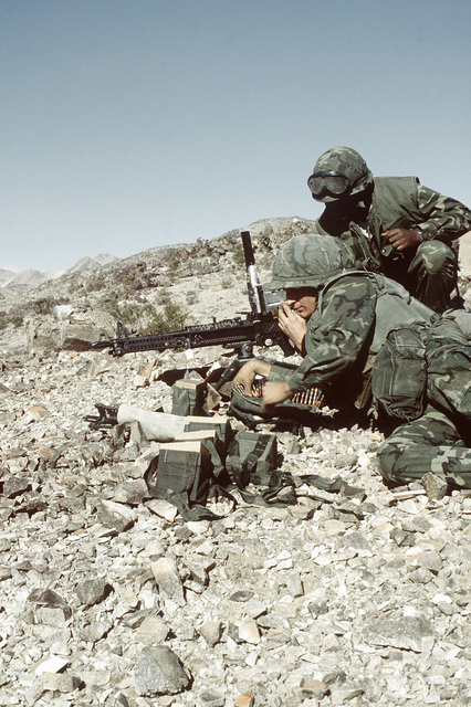 Three combat-ready Marines prepare an M-60A1 machine gun for firing on range 410. This is part of Operation CAX 1-2-82, held at the Marine Corps Air-to-Ground Combat Center